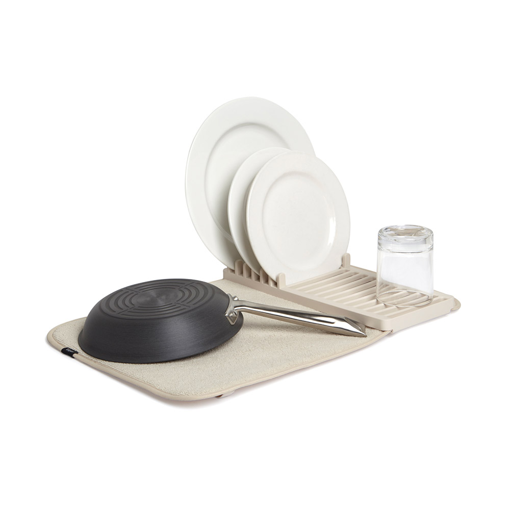 Коврик д/сушки посуды UDRY MINI экрюКоврик для сушки посуды светло-бежевого цвета – компактное изделие из микрофибры с коротким ворсом, легко впитывающее влагу, стекающую с посуды и быстро испаряющее ее, благодаря мембране, прикрепленной снизу. Положив полотно на стол, можно не опасаться, что вода стечет с него и сэкономить время на сушке посуды. Помимо ткани в изделии присутствует практичная пластиковая подставка для тарелок, ложек и вилок, которую можно закрепить на резинке как в середине, так и с краю. Коврик легко складывается в три раза, связывается эластичной лентой и хранится в удобном месте, не занимая много пространства.<br>